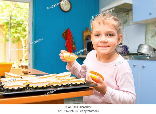 Five-year girl lays on a baking tins Easter cupcakes