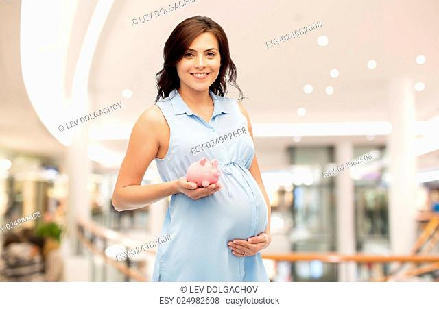 pregnancy, finance, saving, shopping and people concept - happy pregnant woman with piggybank over mall background