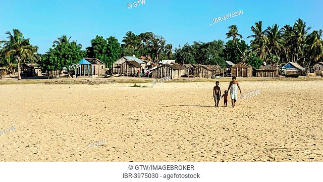 Malagasy woman and her two children walking on the beach, Betany village, Morondava, Toliara province, Madagascar
