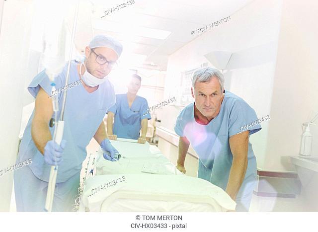 Determined surgeons pushing stretcher down hospital corridor