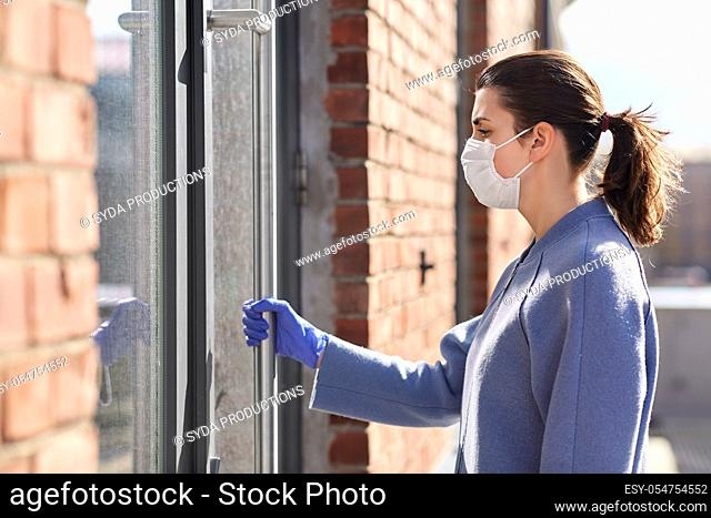 woman in mask and glove holding to door handle