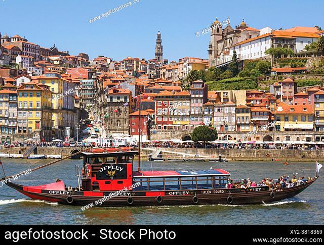 Porto, Porto District, Portugal. View across Douro River from Vila Nova de Gaia to Ribeira district. Boats like this one with tourists enjoying a trip on the...