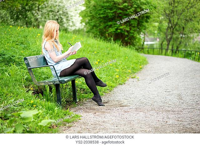One young attractive woman sitting on bench in a park writing in a diary