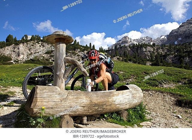 Mountain bike rider filling a water bottle from a water fountain at the Fodara hut in the Fodara Vedla-Mulde, Fanes-Sennes-Prags Nature Park, Trentino