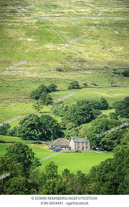 Stone house sits alone against green hills, Yorkshire Dales, UK
