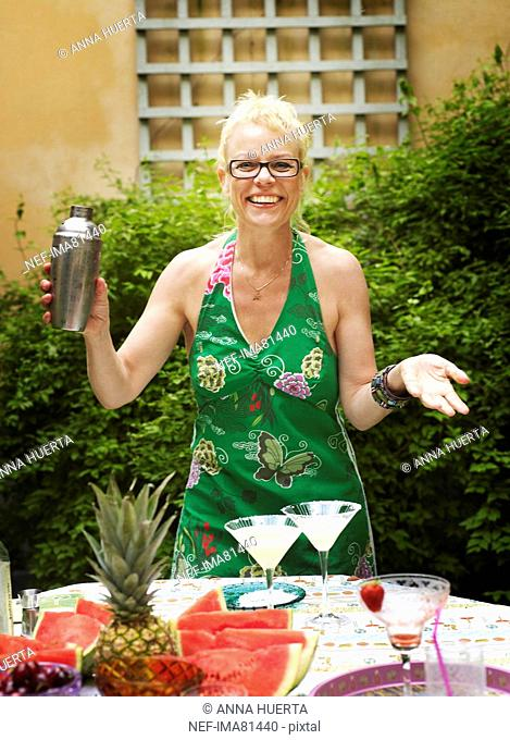 Woman mixing cocktail, smiling