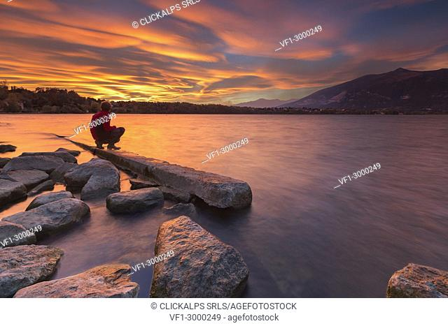 Man admire an incredible sunset of lenticular clouds on lake Annone, Annone di brianza, Lecco province, Brianza, Lombardy, Italy, Europe