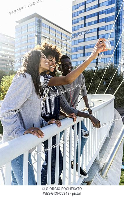 Friends standing on a bridge, taking selfies