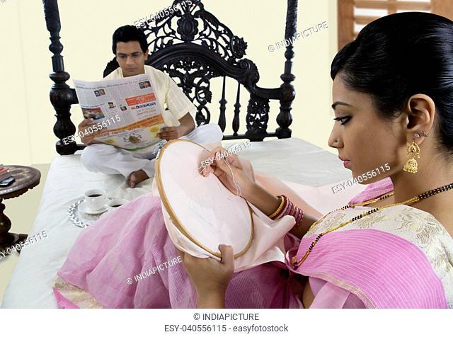 Bengali woman stitching while husband reads newspaper
