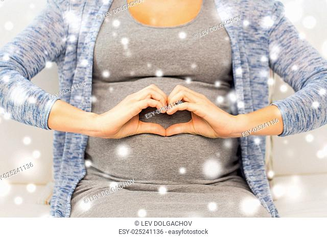 pregnancy, love, care, people and expectation concept - close up of happy pregnant woman making heart gesture at home over snow