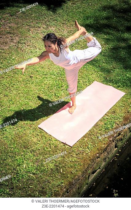 woman making yoga exercise in an old park