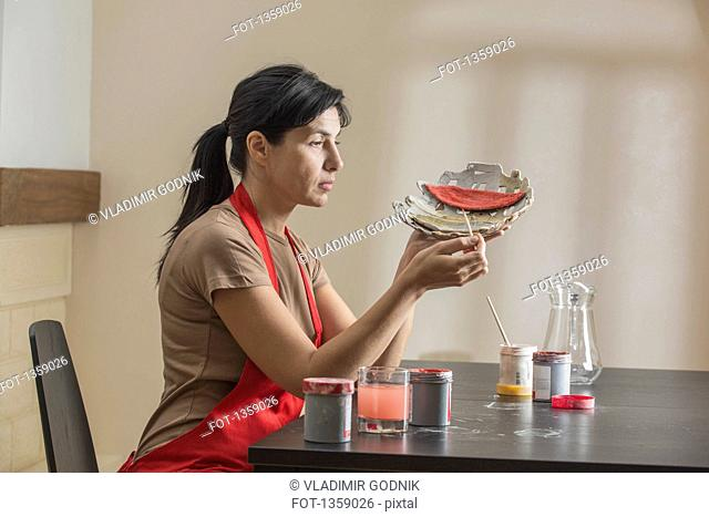 Woman making craft at table in house
