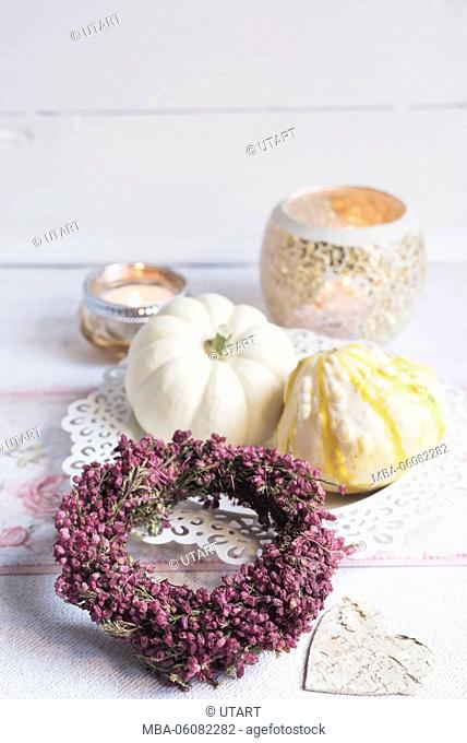 Autumnal still life with light ornamental pumpkins, heather wreath and candles on white background