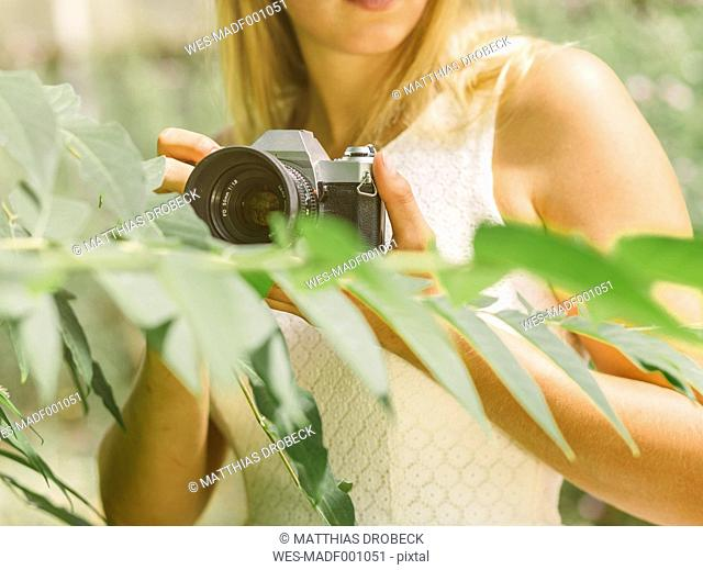 Young woman behind plant holding camera