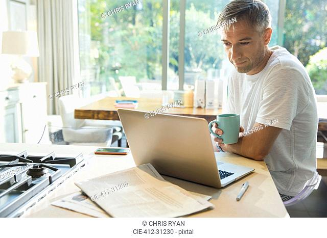Man drinking coffee and working at laptop in kitchen