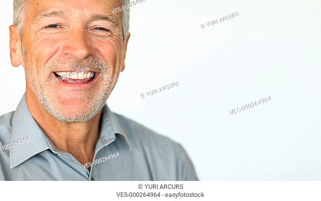 Closeup of a mature man smiling and laughing isolated on white with copyspace