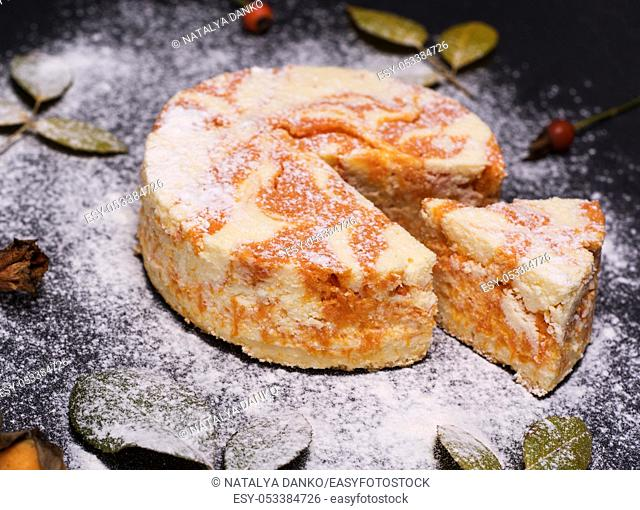 round cheesecake with pumpkin sprinkled with powdered sugar on a black background, top view