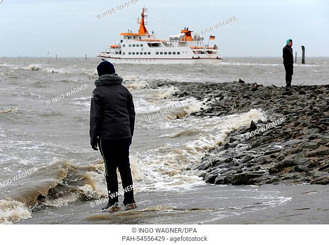 During low water, a boy stands in front of the wind-lashed North Sea next to the mole at the harbor entrance of Bensersiel, Germany, 23 December 2014
