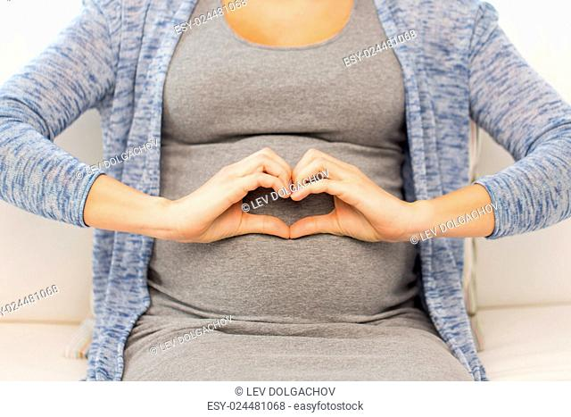 pregnancy, love, care, people and expectation concept - close up of happy pregnant woman making heart gesture at home