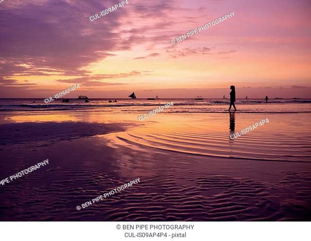 Silhouetted young woman on beach at sunset, Boracay Island, Visayas, Philippines
