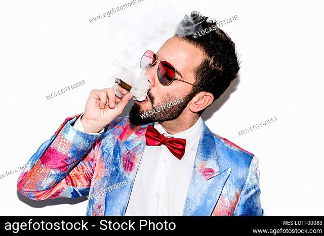 Cool and stylish man wearing a colorful suit and sunglasses and smoking a cigar