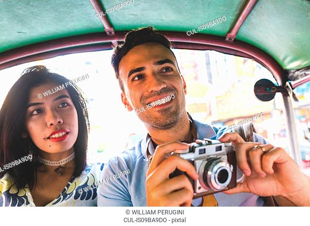 Young tourist couple in auto rickshaw with camera, Bangkok, Thailand