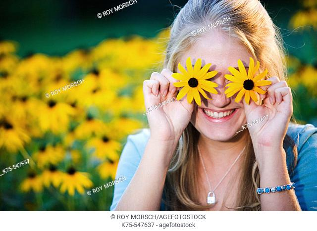 Smiling 17 year old Caucasian blonde teenager with black-eyed susans flowers