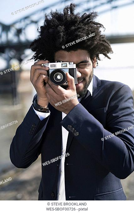 Man in suit at the riverside taking a picture with a vintage camera
