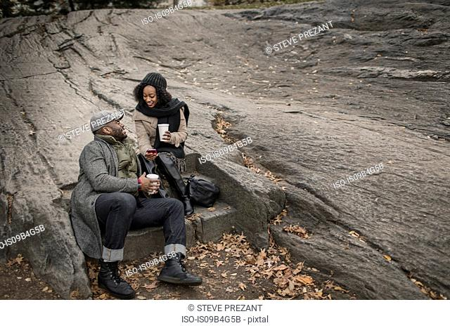 Couple sitting on step in park with takeaway coffee