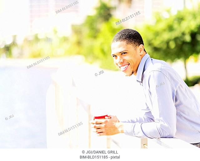 Black businessman leaning on banister at waterfront