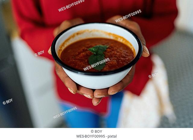 Woman holding bowl of gazpacho