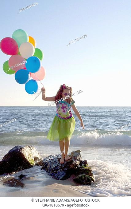young girl standing on rocks with balloons at the ocean