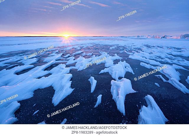 Sun setting over a frozen lake in Ontario, Canada