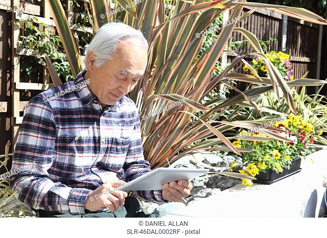 Older man using tablet computer outdoors