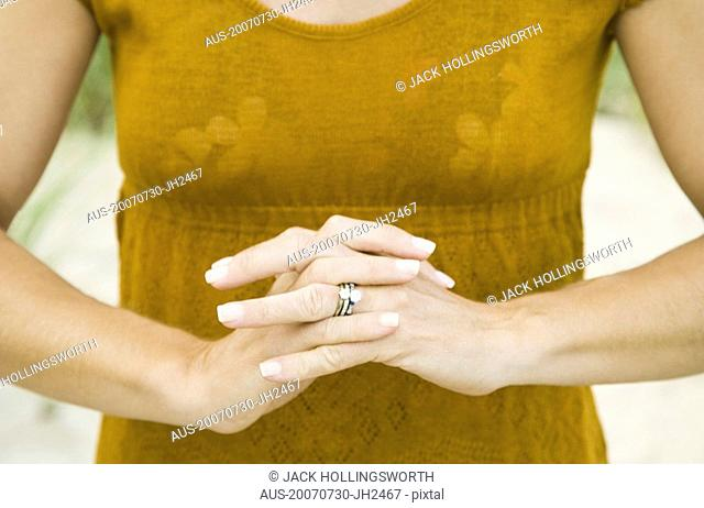 Mid section view of a woman with her hands clasped