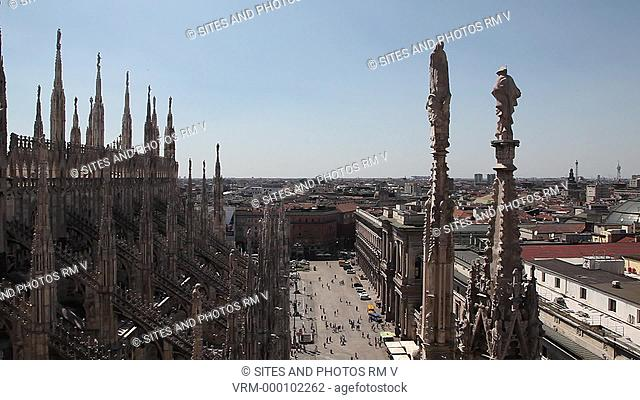 Exterior, Locked Down Shot, Very High Angle, view of the Piazza and street from the cathedral's roof. Seen are the spires and the flying buttresses of the...