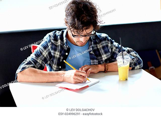 lifestyle, creativity, freelance, inspiration and people concept - creative man with notebook or diary writing and drinking juice at cafe