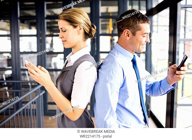 Business people standing back to back while using phone