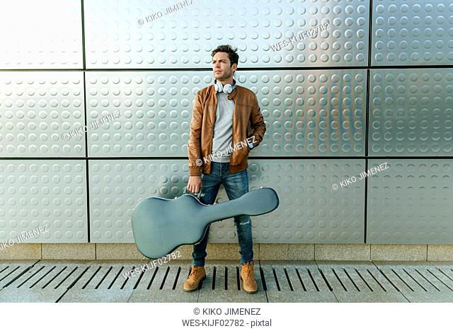 Man with guitar standing in front of a silver wall