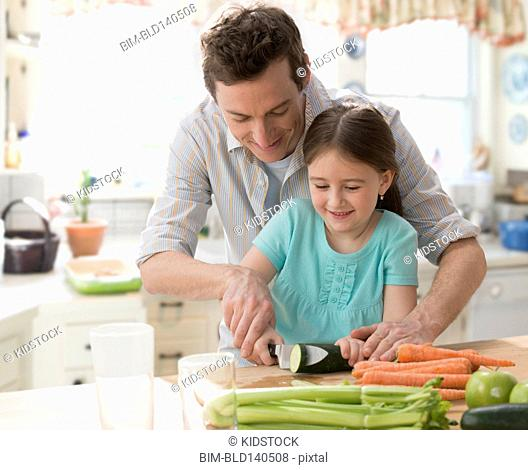 Caucasian father and daughter preparing vegetables