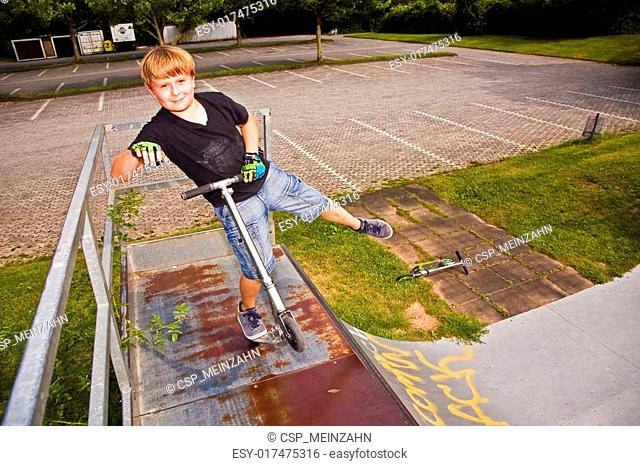 boy is jumping with scooter in pipe