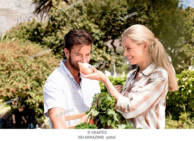 Mature couple in garden, woman holding up fresh onion for man to smell