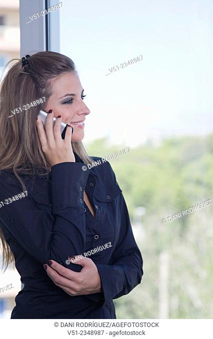 Business woman talking on the phone and looking out the window