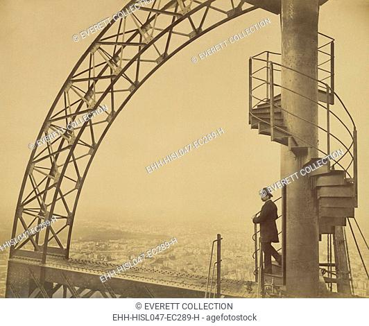 Man standing on the scientific tower of the Eiffel Tower in 1889. Placed the cupola, it was built to extend the life of the temporary monument