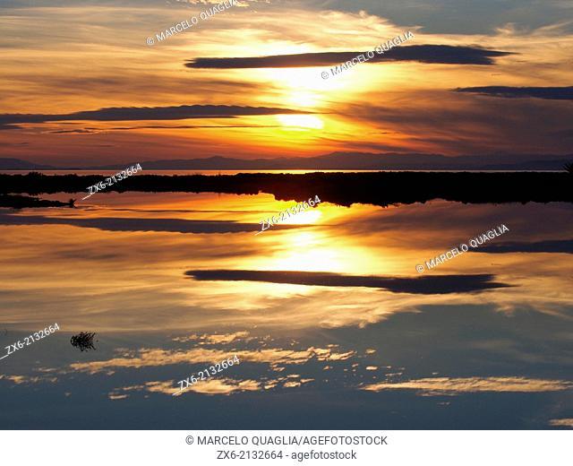Old Tancada Lagoon saltworks and Alfacs Bay at sunset. Ebro River Delta Natural Park, Tarragona province, Catalonia, Spain