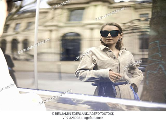 fashionable woman looking at her mirror picture mirrored at car window at street during fashion week, in Paris, France