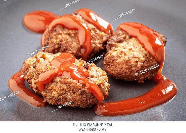 three mini burgers on gray earthenware dish