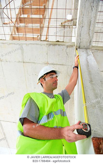 Worker with protective equipment, PPE, Taking measures in concrete beam, retractable tape, housing construction, Basque Country, Spain