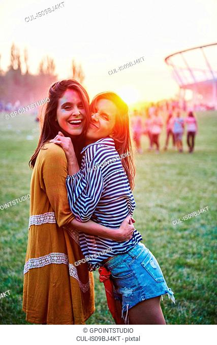 Two young women covered in coloured chalk powder hugging at Holi Festival, portrait
