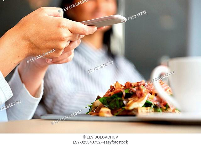 food, dinner, eating, technology and people concept - woman with smartphone and prosciutto ham salad on stone plate at restaurant